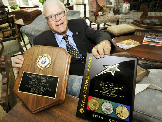 Dr. Paul Scarlata is the recipient of the Knights of Columbus Knight of the Year Award, the plaque for which he received in a ceremony in September. He also previously received the Star Council Award, which he is holding on the right. Dr. Scarlata was photographed Tuesday at his Fayetteville home.