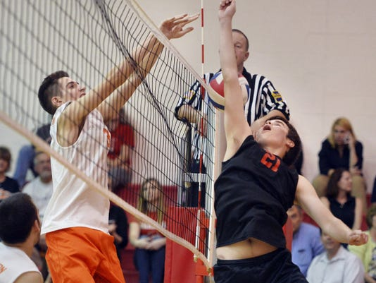 Susquehannock's Stephen Rouse (21) attempts to tip the ball but is foiled by the block of Northeastern's James Toomey (3) during a YAIAA volleyball match Thursday. The Bobcats swept the Warriors in three games.