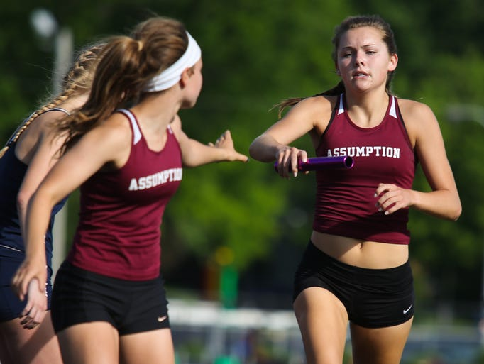 Assumption's Bailey Davis, right, hands off to Sophie Beavin during the 4x800 relay Tuesday evening during the 4A Regionals for track. The winning Assumption team also included Abbie Wright and Sarah Crawford. May 13, 2014
