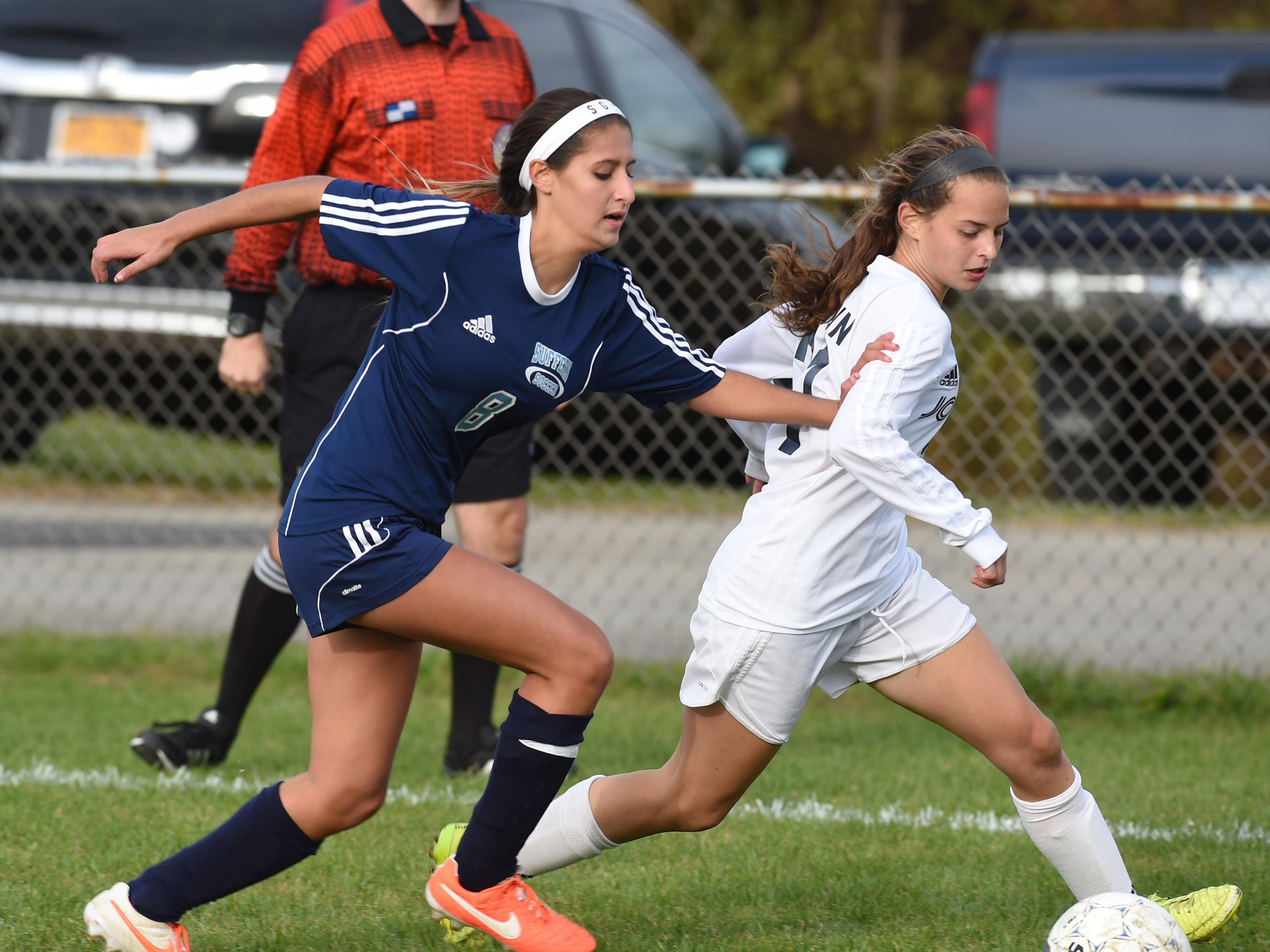 John Jay's Kiley Longin, right, takes the ball down field as Suffern's Jackie Santangelo, left, defends during Tuesday's playoff game.