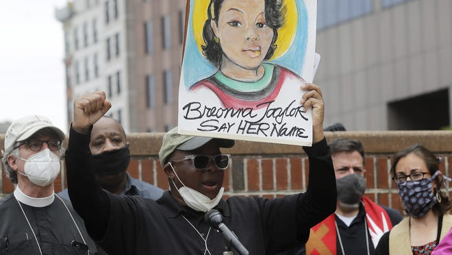 Kevin Peterson, founder and executive director of The New Democracy Coalition, center, displays a placard showing fallen Breonna Taylor as he addresses a rally, Tuesday, June 9, 2020, in Boston. Petersen advocates for changing the name of Faneuil Hall, as its namesake Peter Faneuil, was a slave owner.