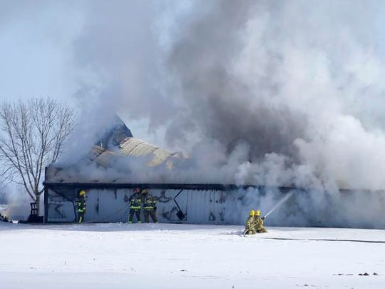 Firefighters work to put out a fire along County Road