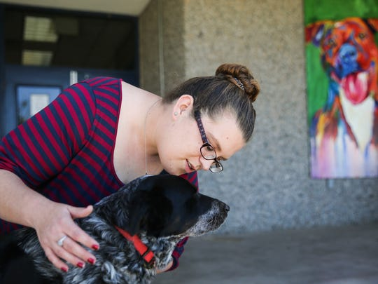 Jenny Murphy, director of adoptions for Concho Valley PAWS, pets her dog in front of the San Angelo Animal Shelter.