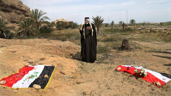 In this April 3, 2015 file photo, an Iraqi man prays for his slain relative, at the site of a mass grave, believed to contain the bodies of Iraqi soldiers killed by Islamic State group militants when they overran Camp Speicher military base, in Tikrit, Iraq,.