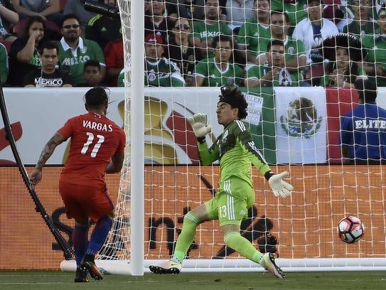 Chile's Eduardo Vargas (L) kicks to score against Mexico's