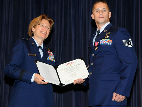 Major General Carol Timmons  presents the Bronze Star medal to Tech. Sgt. Aaron Weber at the New Castle Air National Guard Base in 2015.