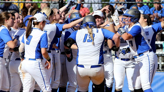 Highlands' Shelby Graybill is greeted at home after hitting a line drive home run over the center field wall.