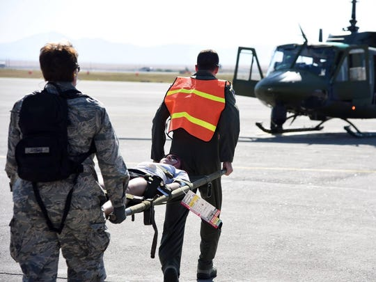 Airmen load a simulated casualty onto a Huey of the 40th Helicopter Squadron at Malmstrom Monday.