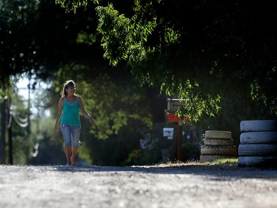 Angela Harrington, 64, takes a walk in her neighborhood,