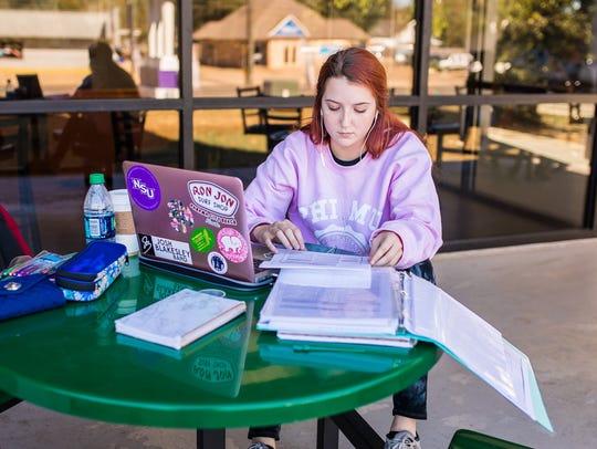 Emily Arnaud, a sophomore nursing major at Northwestern State University, studies outside of Watson Memorial Library.