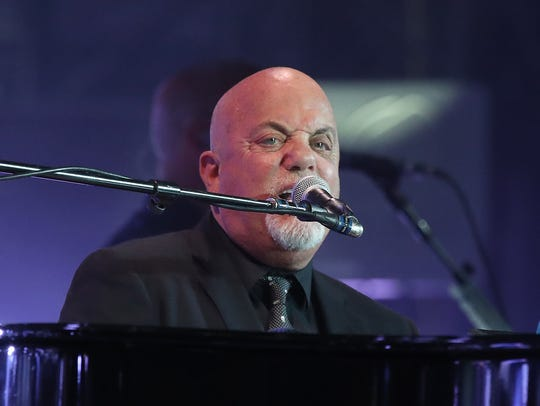 Billy Joel plays during his concert at Lambeau Field