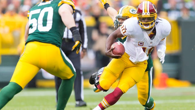 Washington Redskins quarterback Robert Griffin III (10) rushes with the football as Green Bay Packers linebacker A.J. Hawk (50) defends during the first quarter at Lambeau Field.