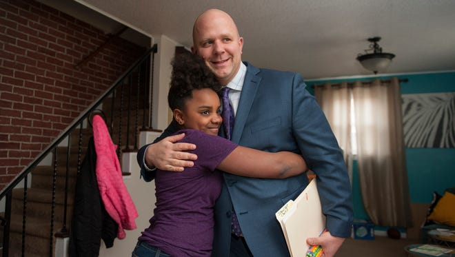 Tom Braddock, principal of Evergreen Avenue Elementary School in Woodbury, is hugged by fifth-grader Melania Kee as Braddock visited Kee's home Friday afternoon to present her with a certificate and a special pencil to honor her for being a standout student of the week.