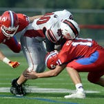 Hilton's Ted Lawson, center, is sandwiched between Fairport's Michael DeWind, left, and Kyle McAvoy during the season opener played at Fairport High School on Saturday, September 5, 2015. Hilton beat Fairport 40-28.