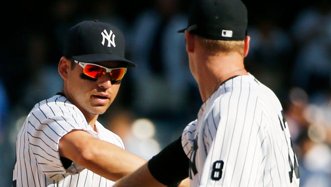 New York Yankees center fielder Jacoby Ellsbury, left, celebrates with third baseman Chase Headley after the Yankees defeated the Toronto Blue Jays 5-3 in a baseball game in New York, Monday, Sept. 5, 2016.