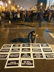A lone protester creates a pattern of signs as others occupy an intersection during a march through the streets of St. Louis protesting against recent shootings of young black men by law enforcement officers, early Monday, Oct. 13, 2014.