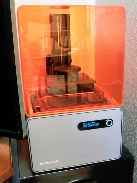 Pictured is a rapid prototyping machine Alfonso Luna Jr. uses to create models in the process of making his jewelry. Inside the tank is photo sensitive liquid resin. A laser draws a picture of the ring he has created on the liquid. Wherever it draws, it solidifies and creates the shape.