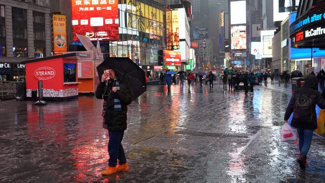 People are reflected in the snow covered street in Times Square in New York on Wednesday,