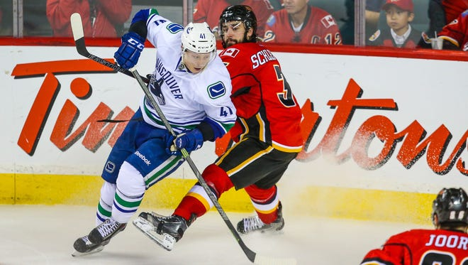 Vancouver Canucks left wing Ronalds Kenins (41) and Calgary Flames defenseman David Schlemko (3) battle for the puck during the second period in game four.