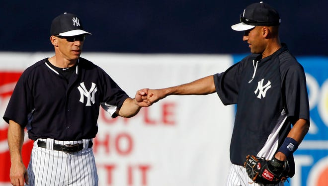 New York Yankees manager Joe Girardi (28) and shortstop Derek Jeter (2) fist bump prior to the spring training game against the Baltimore Orioles.