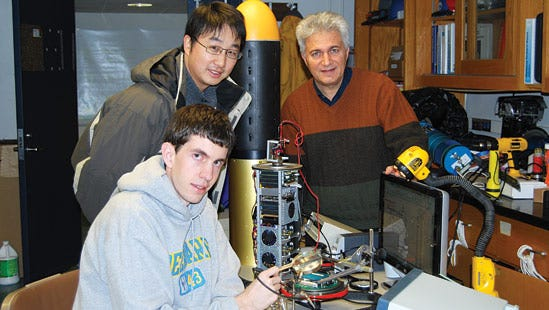 In this 2009 photo, Moshen Badiey, Aijun Song, and first-year Ph.D. student Justin Eickmeier (front), work on UD's autonomous underwater vehicle.