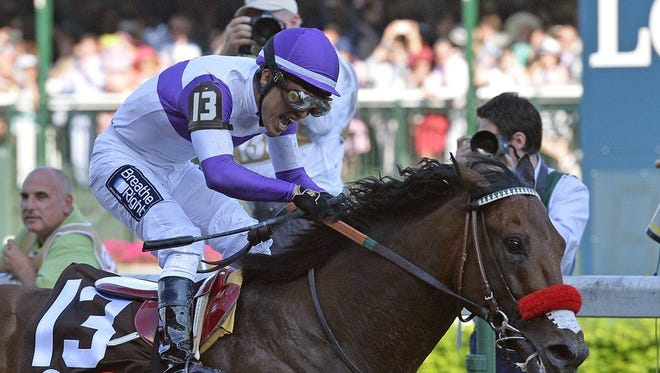 Mario Gutierrez celebrates atop Nyquist as they cross the finish line at Kentucky Derby 2016.