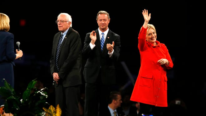 Democratic presidential candidates Bernie Sanders (from left), Martin O'Malley and Hillary Clinton look out over the crowd Saturday, Oct. 24, 2015, at the start of the Jefferson Jackson dinner in Des Moines.
