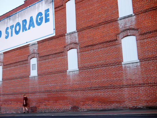 A shot from the film, with the main character, Gracie walking beside this storage building.