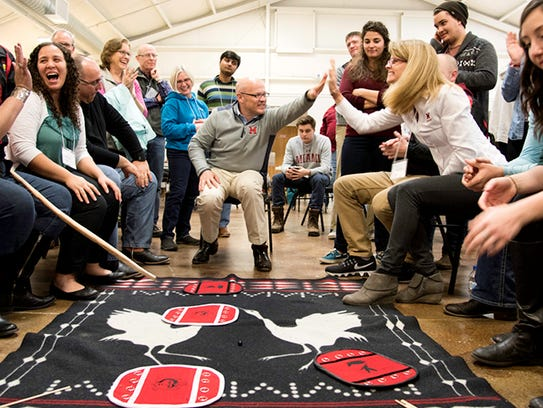 Miami University President Gregory Crawford and his wife, Renate Crawford, play a traditional Miami Tribe moccasin game at the Myaamia Council House in Miami, Oklahoma.