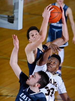 East Lansing's Brandon Johns, rear, grabs a rebound over Holt's Ar'tavious King, center, and East Lansing's Noah Schon Friday, Feb. 17, 2017, in Holt, Mich. East Lansing won 66-61.