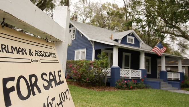 A realty sign hangs in front of a home for sale in Orlando, Fla.