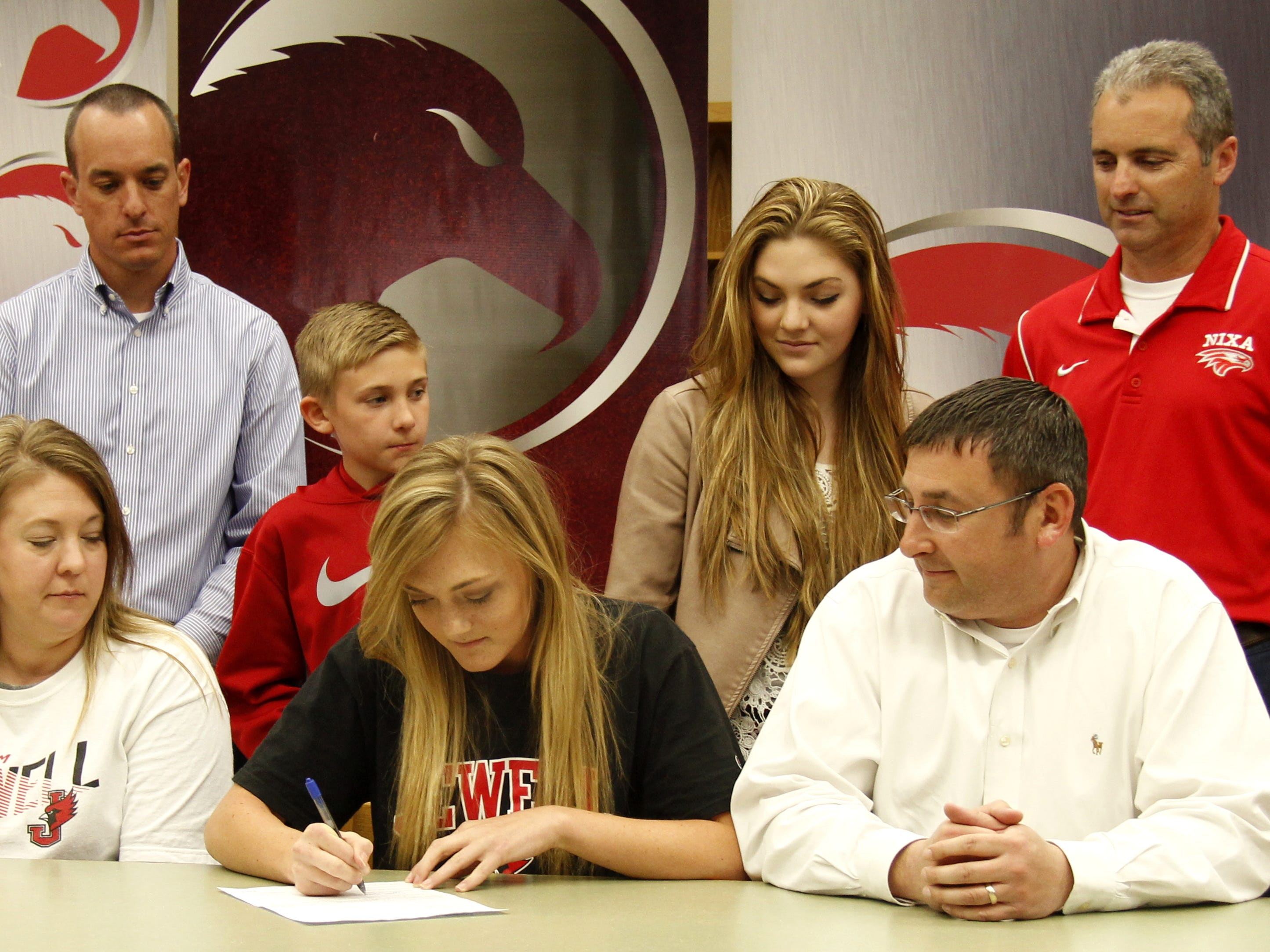 Nixa soccer player Alyson Galler (center), surrounded by her family and coaches, signs a letter of intent to play for William Jewell College next year during a ceremony Wednesday at Nixa High School.
