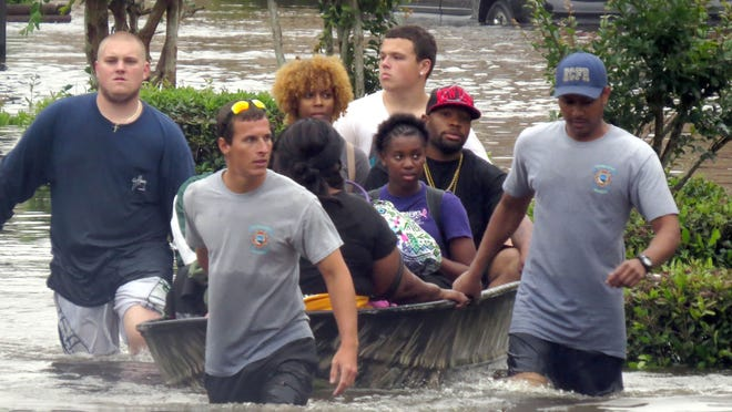 Residents of the Forest Creek Apartments are rescued by Escambia County firefighters and emergency services personnel by boat Wednesday morning. Heavy rains moved throughout the area Tuesday night flooded nearly all of the apartment blocks in the complex.