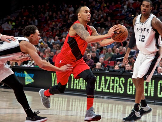 Portland Trail Blazers guard Shabazz Napier, center, dribbles past San Antonio Spurs guard Bryn Forbes, left, and San Antonio Spurs forward LaMarcus Aldridge, right, during the first half of an NBA basketball game in Portland, Ore., Sunday, Jan. 7, 2018. (AP Photo/Craig Mitchelldyer)