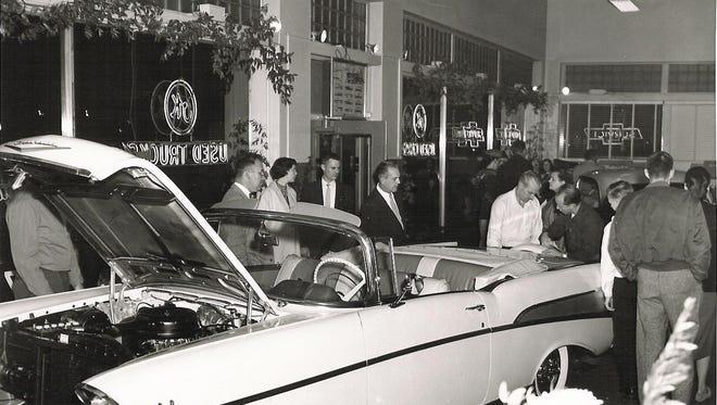New car announcement Bud Kouts showroom in Lansing, 1957. (1957 Belair Convertible).