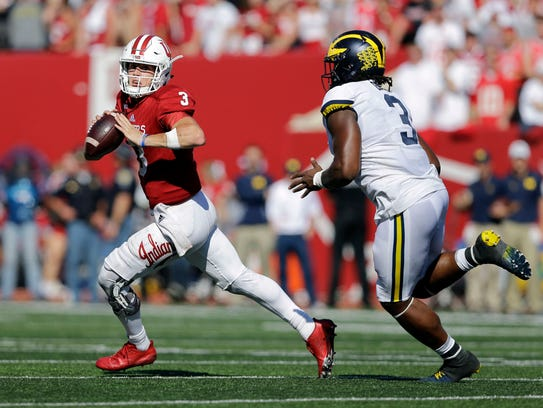 Indiana quarterback Peyton Ramsey, left, runs from