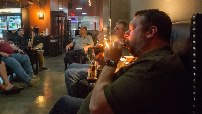 Customers enjoy their cigars at the new lounge location Jerry's Cigar Shop opened on Kerry Forrest Parkway.