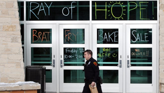 A Sheboygan police officer leaves Sheboygan North after getting some items a the Ray of Hope brat fry benefit Friday, Feb. 12,  at North. The event was a combined effort of North High, Farnsworth Middle School and Lake Country Academy to help Sheboygan Falls' Maki family who lost three children to a house fire in January.