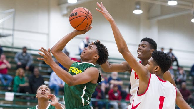 Indianapolis Crispus Attucks High School senior Nike Sibande (22) goes through the Manual defense to score during the first half of an IHSAA high school basketball game Saturday, Jan. 21, 2017, at Arsenal Tech High School. Four teams competed in the semi-final round of the Indianapolis City Boys Basketball Tournament.