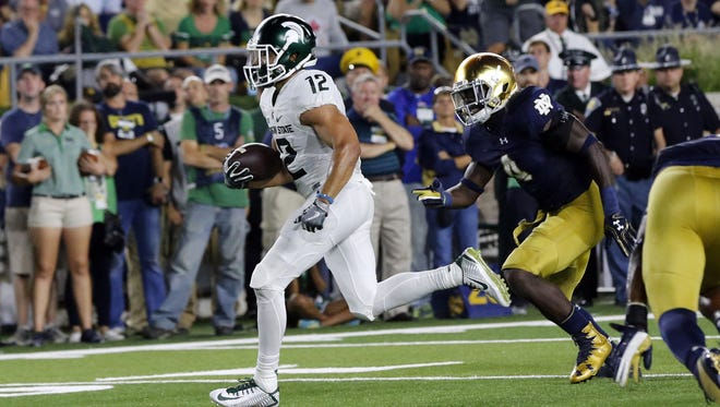 Michigan State Spartans receiver R.J. Shelton scores a 10-yard touchdown in front of Notre Dame linebacker Te'von Coney. Shelton caught a short toss from Tyler O'Connor on the play.