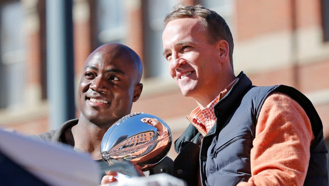 Denver Broncos quarterback Peyton Manning and defensive end DeMarcus Ware held the Lombardi Trophy during a parade for the Super Bowl champions on Feb. 9 in Denver.