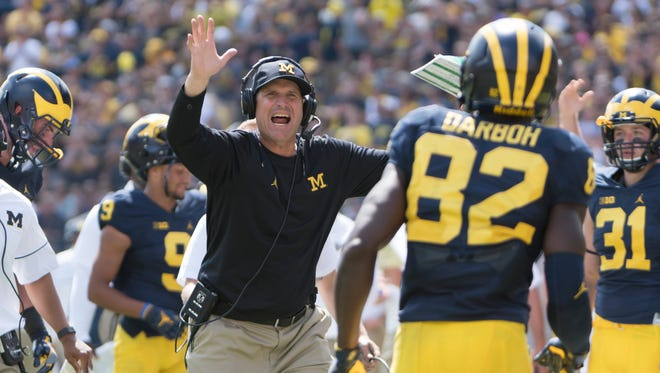 Michigan coach Jim Harbaugh greets his players on the sideline after a first-half touchdown on Saturday.
