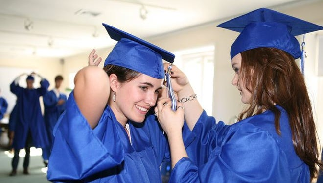 Diane DeVignemont has her tassel straightened out by Romane Mizeret as the French American School of New York celebrates their 2014 graduation at the Wainwright House in Rye, June 15.
