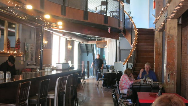 The long bar and dining room at Menagerie pop-up restaurant in Pontiac are strung with white lights.