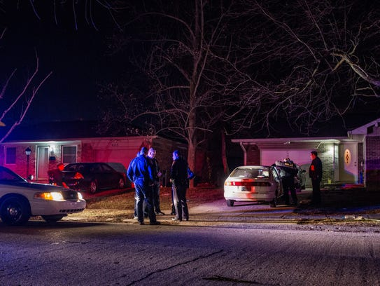 IMPD officers and investigators gather outside a home