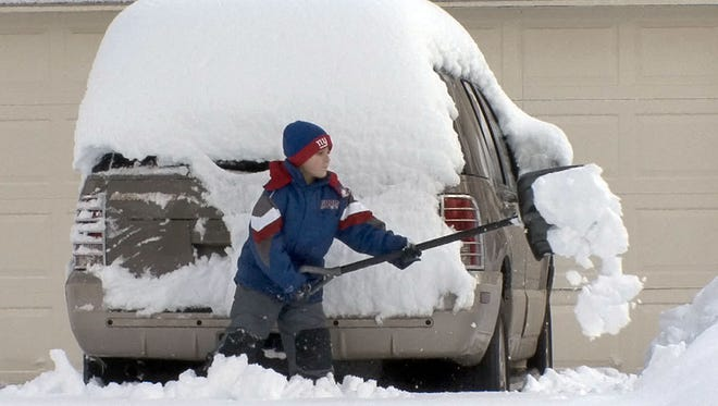 Michael Kuver, 10, Manalapan, cleans snow from around his grandfather's car on Tennent Road in Manalapan Thursday.  1/27/11 - MANALAPAN - MANALSNOW0127A - ASBURY PARK PRESS PHOTO BY THOMAS P. COSTELLO - WITH VIDEO