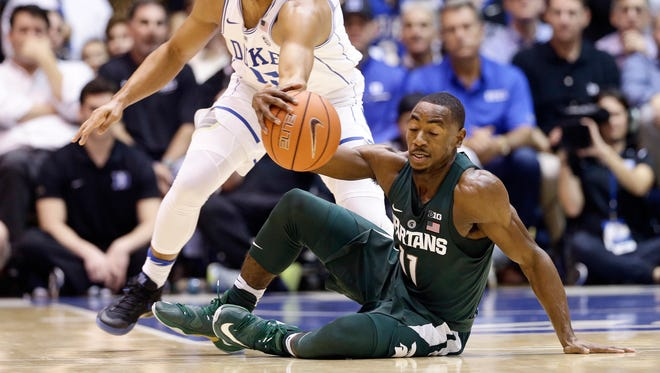 Duke's Frank Jackson and Michigan State's Lourawls Nairn Jr. (11) reach for the ball during the first half Tuesday in Durham, N.C.