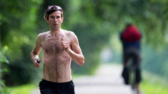 Scott Spitz, an avid runner and strict vegan who has run a 2:25:55 marathon, runs on Indianapolis' tow path, near Butler University on Monday, June 16, 2014. He was diagnosed with a rare cancer in early 2013. Runner's World magazine named him the male winner of their 2014 cover contest.