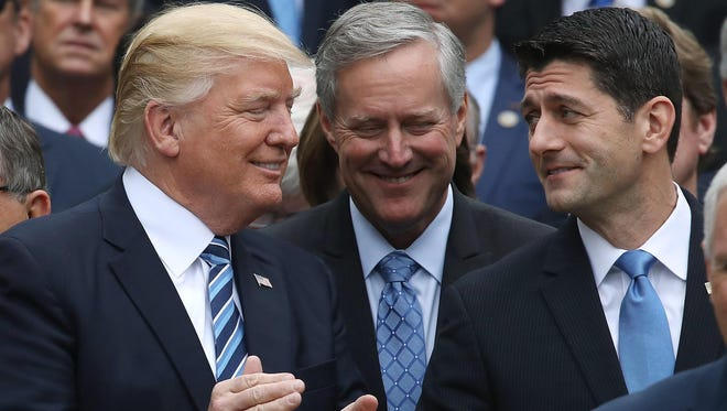 President Donald Trump (left) stands with House Speaker Paul Ryan (R-Wis.) (right) and Freedom Caucus Chairman Mark Meadows (R-N.C.), after Republicans passed legislation aimed at repealing and replacing Obamacare during an event in the Rose Garden at the White House on May 4.