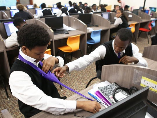 Elijah Kirby ties his tie with help from Gianni Simmons in the learning center at Carpe Diem's Aiken Campus, which opened in August 2013.